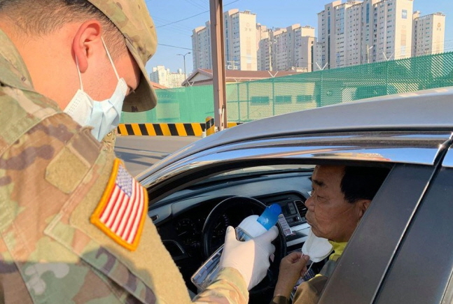 In this photo, uploaded on U.S. Army Garrison Daegu's Facebook account on April 3, 2020, a service member conducts a smell test on an entrant to one of its bases as part of efforts to screen possible coronavirus patients.