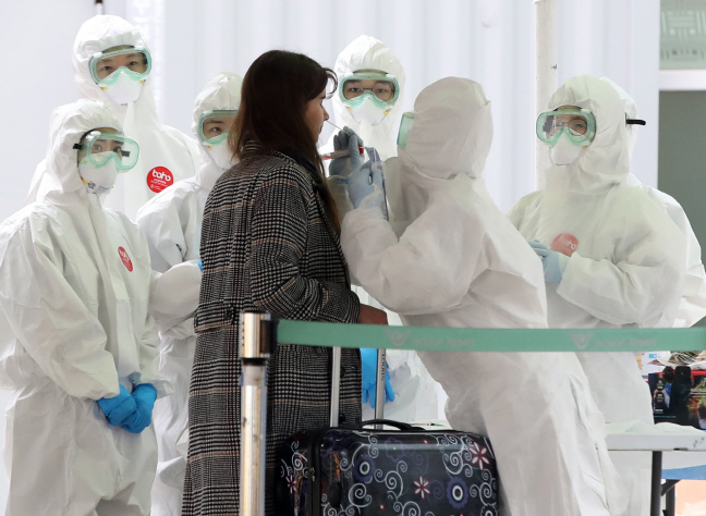 A woman, assumed to be an overseas entrant, is screened by health authorities at an open walk-through screening center at Incheon International Airport, west of Seoul, on March 26, 2020. (Yonhap)