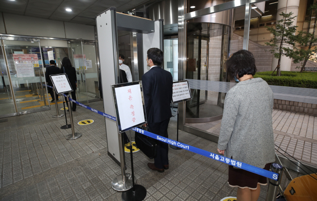 People keep their distance and practice social distancing as they wait in a line to enter a courthouse in southern Seoul on March 30, 2020. (Yonhap)