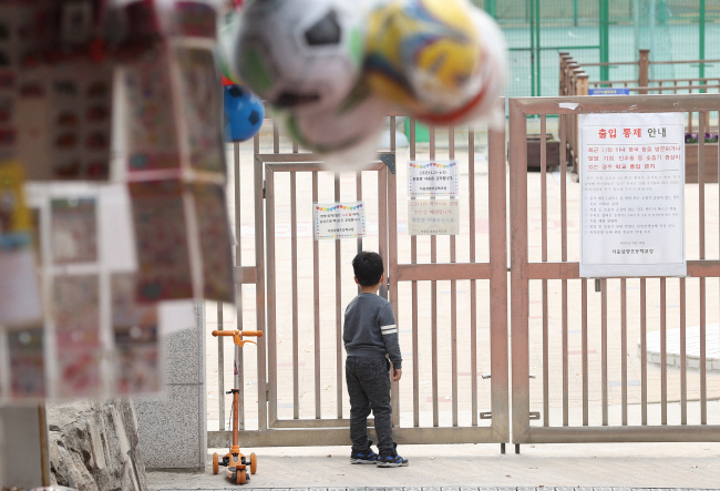 A boy looks through closed gates at an elementary school in the Yongsan district of central Seoul on March 31, 2020. (Yonhap)