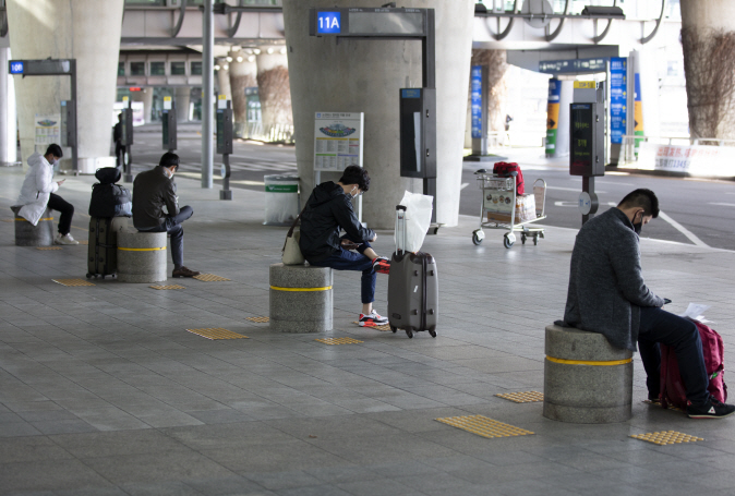 People maintain a distance from one another while waiting for buses to avoid potential COVID-19 infection at a terminal of Incheon International Airport, west of Seoul, on April 6, 2020. (Yonhap)
