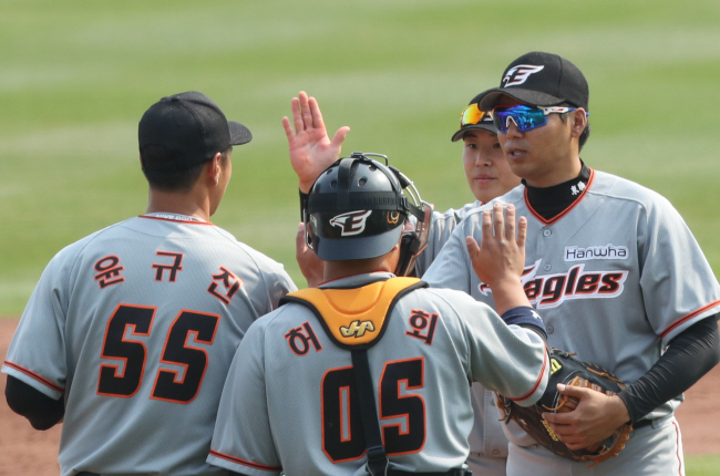 Members of the Hanwha Eagles high-five each other at the end of their intrasquad game at Hanwha Life Eagles Park in Daejeon, 160 kilometers south of Seoul, on April 7, 2020. (Yonhap)