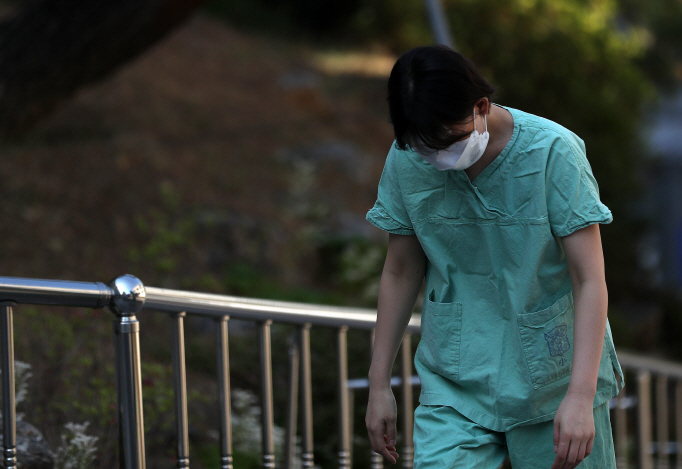 A medical worker looks tired after completing a shift for the service of people infected with the new coronavirus at a hospital in the southeastern city of Daegu on April 8, 2020. (Yonhap)
