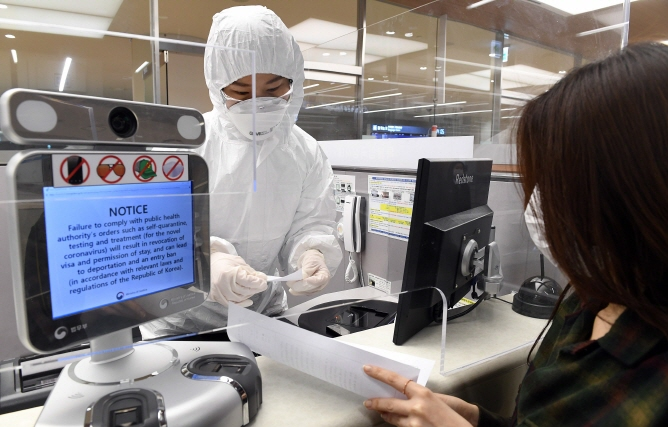 An immigration official, clad in a full set of protective gear, gives instructions to a passenger about self-quarantine procedures at Incheon International Airport, west of Seoul, on April 8, 2020. (Yonhap)