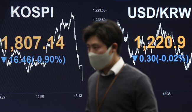 A currency dealer wearing a mask walks past an electronic board in the trading room of KB Kookmin Bank in Seoul on April 8, 2020. (Yonhap)