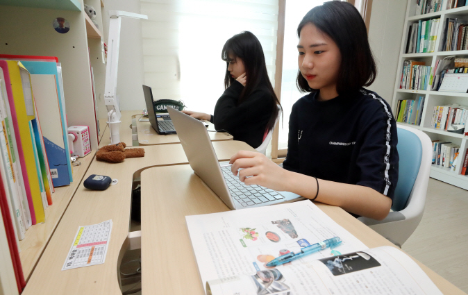 Twin sisters Park Ha-neul and Park Ga-eul, who are both seniors at middle schools, take online classes at their home in the western Seoul ward of Yangcheon on April 9, 2020. (Yonhap)