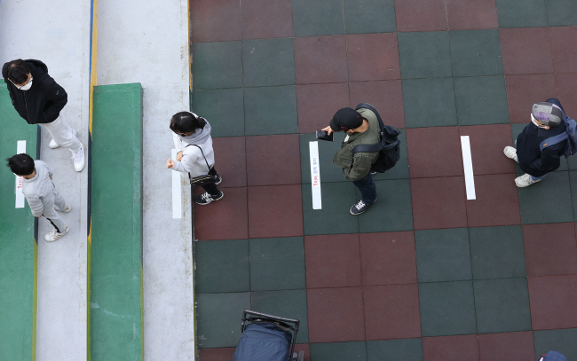 Voters stand 1 meter apart from each other as they wait to cast their ballots at a polling station in the eastern Seoul ward of Seongdong on April 10, 2020. (Yonhap)