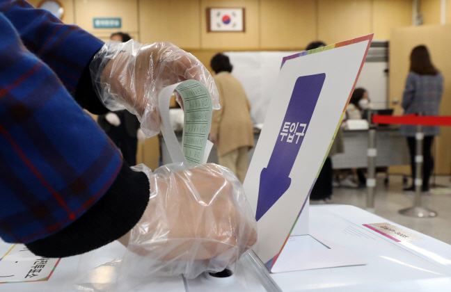 A voter casts a ballot at a polling station in the southeastern Seoul ward of Gangnam on April 10, 2020. (Yonhap)