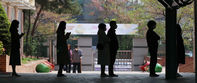 People stand apart from each other at an elementary school in Songpa Ward, southeastern Seoul, as they wait to vote in the general elections on April 15, 2020. (Yonhap)