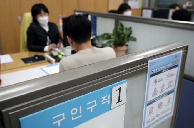 The file photo, shows a job seeker looking at recruitment notices at an employment center in Seoul. (Yonhap)