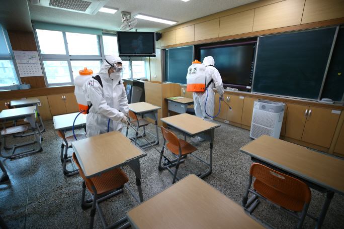 Military officials carry out a disinfection operation at a middle school in Daegu, some 300 kilometers south of Seoul, to prevent the spread of the new coronavirus. (Yonhap)