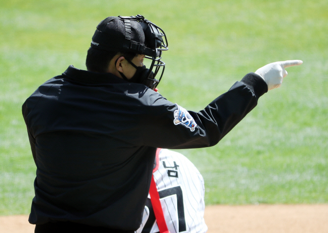 Home plate umpire Oh Hoon-gyu calls a strike with a gloved hand while wearing a mask during a Korea Baseball Organization preseason game between the LG Twins and the Doosan Bears on April 21, 2020. (Yonhap)