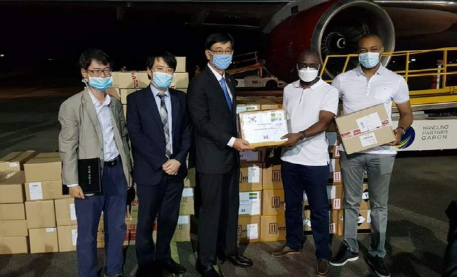This photo, provided by the South Korean Embassy in Gabon, shows Gabonese government officials (1st and 2nd from R) posing for a photo upon the arrival of 50,000 coronavirus test kits from South Korea at Libreville International Airport in the Gabonese capital city of Libreville on April 18, 2020.