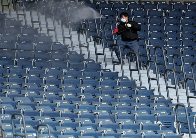 A stadium official disinfects seats at Jamsil Baseball Stadium in Seoul in this photo taken April 24, 2020. (Yonhap)