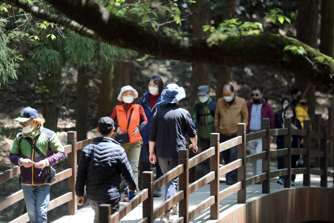 Citizens wearing face masks walk in a park in Busan on April 26, 2020. (Yonhap)