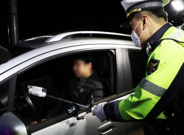 A police officer conducts a roadside breath test using a contactless breathalyzer designed to protect testers from coronavirus infections at an intersection in Gwangju, Gyeonggi Province, on April 18, 2020. (Yonhap)