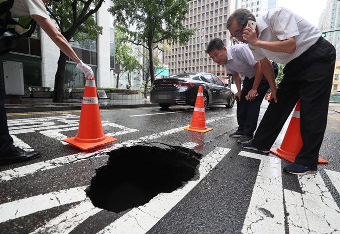 Officials inspect a sinkhole on a road in Seoul's Jung Ward on Aug. 1, 2019, after a torrential rain hit the city the previous day. (Yonhap)