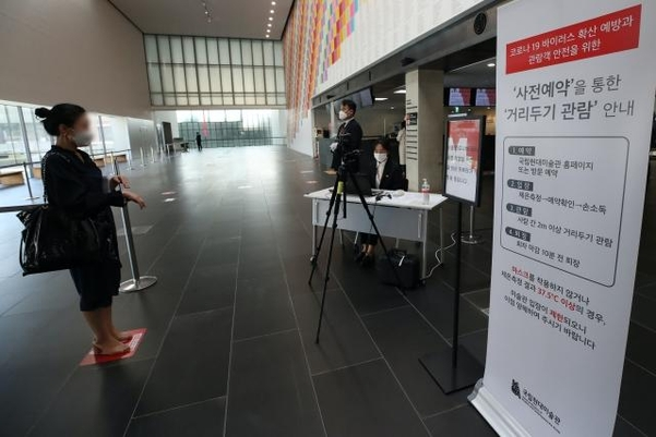 An official at the Seoul branch of the National Museum of Modern and Contemporary Art conducts a fever test on a visitor on May 7, 2020. (Yonhap)