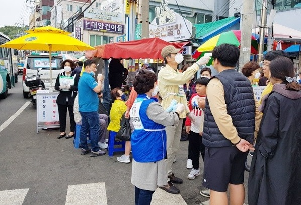 This photo provided by the city of Tongyeong shows local officials and volunteers holding a hand sanitation campaign at a market in the southwestern coastal city on May 3, 2020.