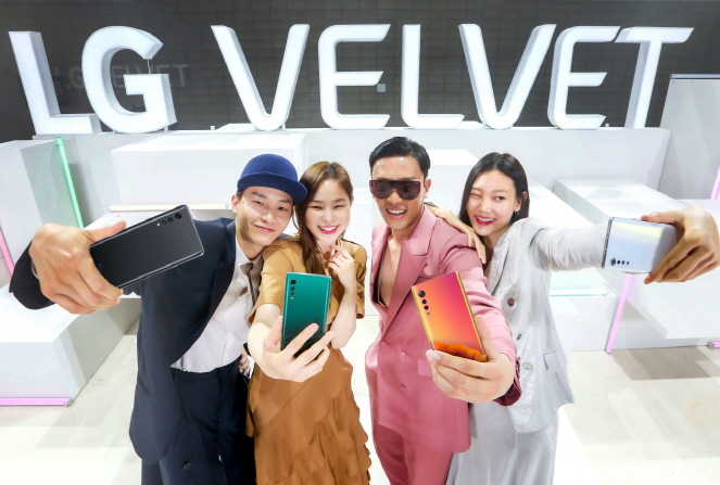 In this photo provided by LG Electronics Inc. on May 7, 2020, models introduce the company's new smartphone, LG Velvet, at its launching event in Seoul.
