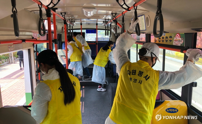 This photo provided by the city of Tongyeong shows volunteers cleaning and disinfecting a city bus in the southwestern coastal city on May 4, 2020.
