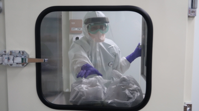 This file photo provided by the Korea Nurses Association shows a nurse at the Pohang Medical Center delivering food to COVID-19 patients being treated inside a negative pressure chamber.