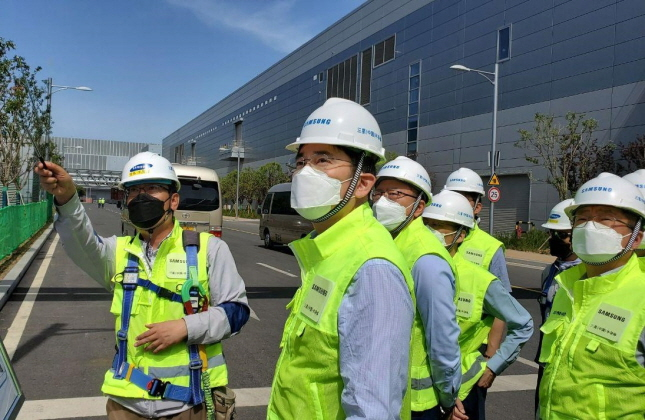 This photo, provided by Samsung Electronics Co. on May 18, 2020, shows Samsung Electronics Vice Chairman Lee Jae-yong (C) inspecting the company's semiconductor plant in Xian, China.
