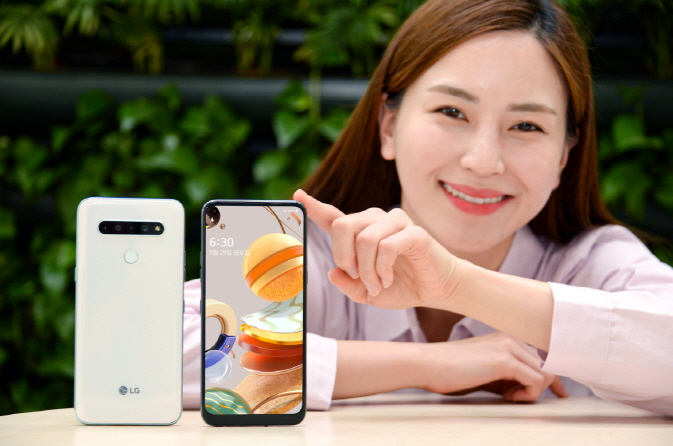In this photo, provided by LG Electronics Inc. on May 21, 2020, a model introduces LG's new budget smartphone, the Q61.