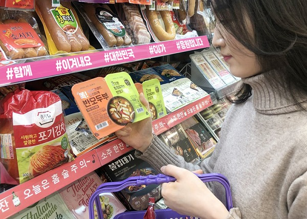 This undated photo, provided by the convenience store chain CU, shows a consumer looking at tofu at CU.