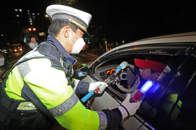 A police officer conducts a sobriety test on a driver with a sensor on a stick in Seoul on May 19, 2020. (Yonhap)