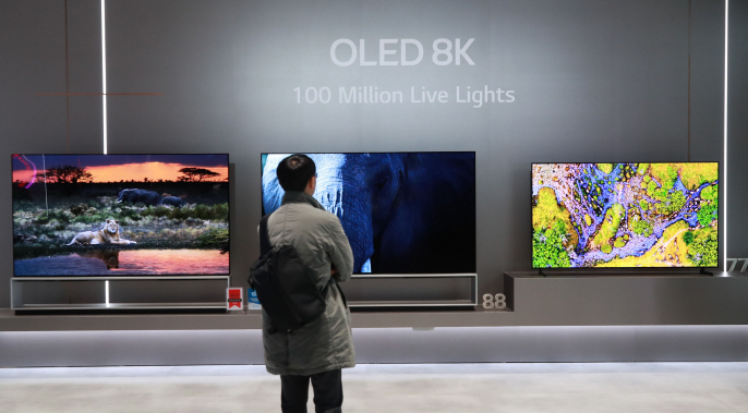 This photo taken on Jan. 7, 2020, shows a reporter looking at LG Electronics Inc.'s OLED 8K TVs at the company's exhibition booth at the Consumer Electronics Show in Las Vegas, Nevada. (Yonhap)