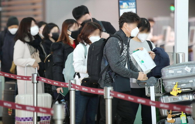 This photo taken on Feb. 7, 2020, shows outbound passengers wearing masks waiting in a queue to undergo departure procedures at Incheon International Airport in Incheon, just west of Seoul. (Yonhap)