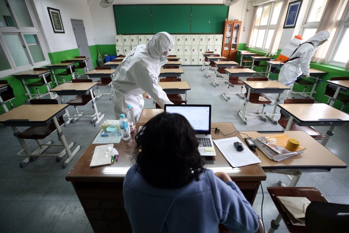 This photo, taken on April 16, 2020, shows a teacher running an online class in an empty classroom in the southern city of Daegu as soldiers clean it with disinfectants. (Yonhap)