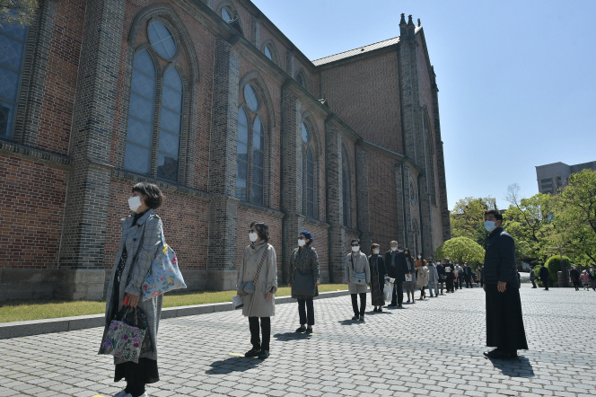 People wait in line to participate in a Mass at Myeongdong Cathedral in central Seoul on April 26, 2020, in this file photo. (Yonhap)