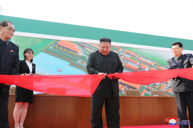 North Korean leader Kim Jong-un (C) cuts a ribbon during a ceremony to mark the completion of a phosphatic fertilizer factory in Sunchon, north of Pyongyang, on May 1, 2020, in this photo released the next day by North Korea's official Korean Central News Agency.