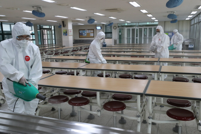 Health authorities disinfect a high school cafeteria in the southeastern Seoul ward of Songpa on May 6, 2020. (Yonhap)