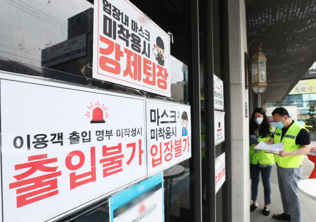 Local government officials post entry restriction signs and warnings that masks must be worn at all times at a club in Suwon, 46 kilometers south of Seoul, on May 11, 2020. (Yonhap)