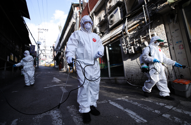 Volunteers carry out disinfection operations in the popular neighborhood of Itaewon in Seoul on May 12, 2020. (Yonhap)
