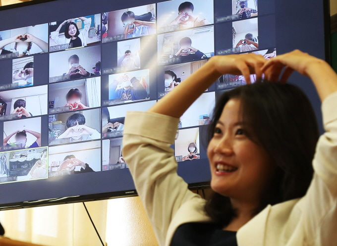 A teacher makes a heart with her arms during an online class at Unjung Middle School in Seongnam, south of Seoul, on May 14, 2020, one day ahead of Teachers' Day, as her students gesture back at her. (Yonhap)
