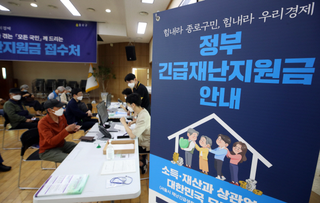 People wait at a community service center in Seoul's Jongno Ward on May 18, 2020, to apply for the government's emergency relief funds. (Yonhap)