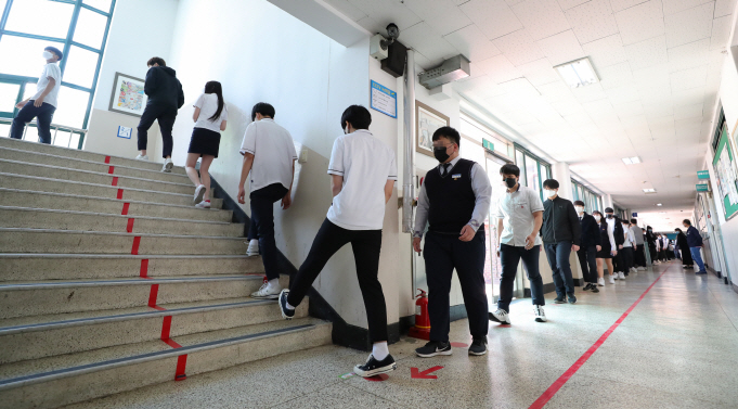 Students at a high school in Seoul wait in line to enter a cafeteria while keeping distance from each other on May 20, 2020. (Yonhap)