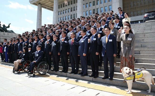 In this photo taken on May 20, 2020, first-time lawmakers-elect pose in front of the National Assembly in Seoul. (Yonhap)