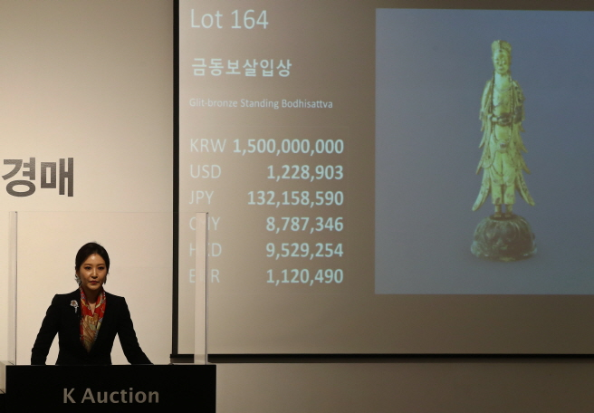 An auctioneer presents Gilt-bronze Standing Bodhisattva, which was made between the 6th and 7th centuries during the Silla period, at K Auction in southern Seoul on May 27, 2020. (Yonhap)