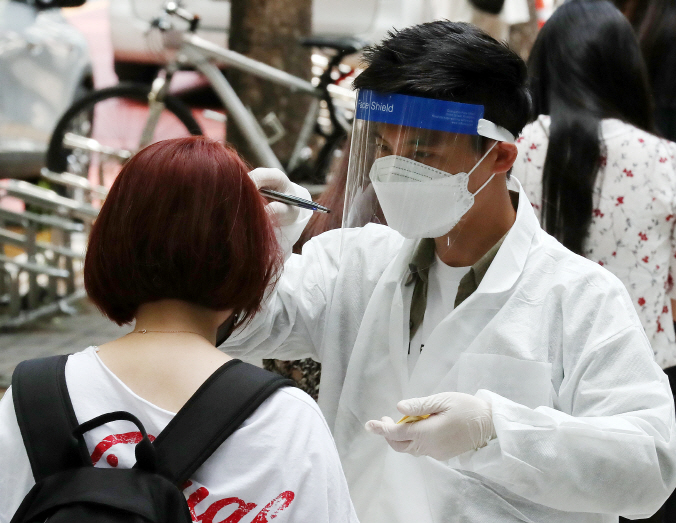 A health worker checks a visitor's temperature at a virus screening center set up in Bucheon, just west of Seoul, on May 28, 2020. (Yonhap)