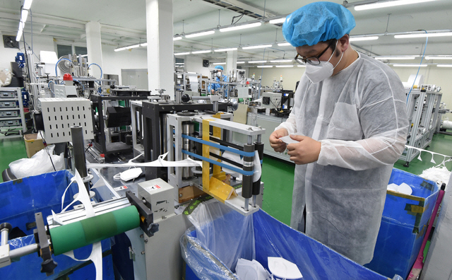 In this file photo, taken on March 9, 2020, a worker checks a production line for masks at a facility in Yongin, just south of Seoul. (Yonhap)