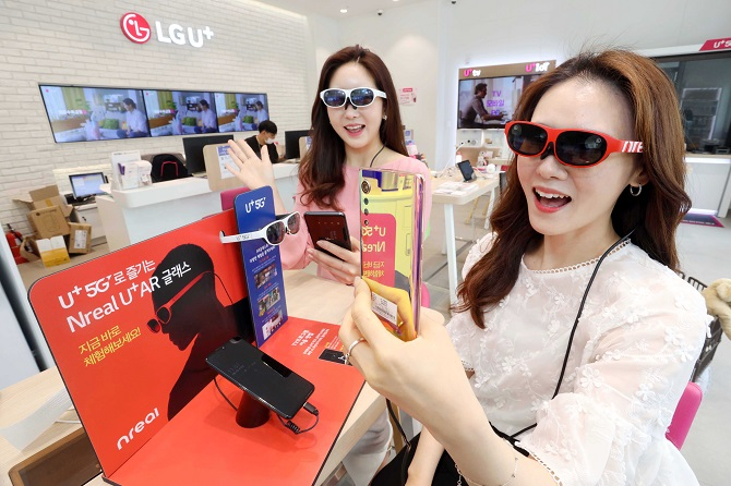 This photo, provided by LG Uplus Corp. on June 4, 2020, shows models using the Nreal Light AR glasses, which LG Uplus plans to launch in the third quarter of the year.