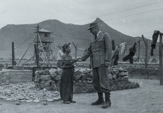A little boy shakes hands with an ICRC official with a broad smile on his face at a POW camp in Geoje in a photo taken by the ICRC on June 4, 1951. (Yonhap)