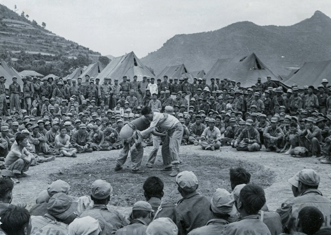 A crowd of POWs gather to see a traditional Korean wrestling match at the Geoje camp in a photo taken by the ICRC in June 1951. (Yonhap)