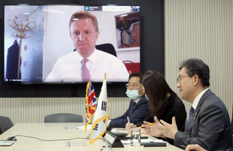This file photo provided by the culture ministry shows Park Yang-woo (R), South Korean culture minister, holding a video conference meeting with his British counterpart, Oliver Dowden (on monitor), at the government complex in Seoul on June 3, 2020.