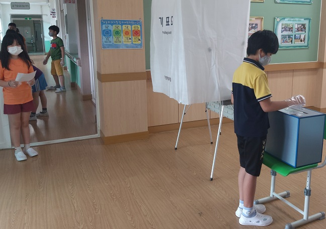 Students lined up as they maintained proper physical distancing from each other, wearing plastic gloves before voting at the booth. (image: Yeongdong Office of Education)